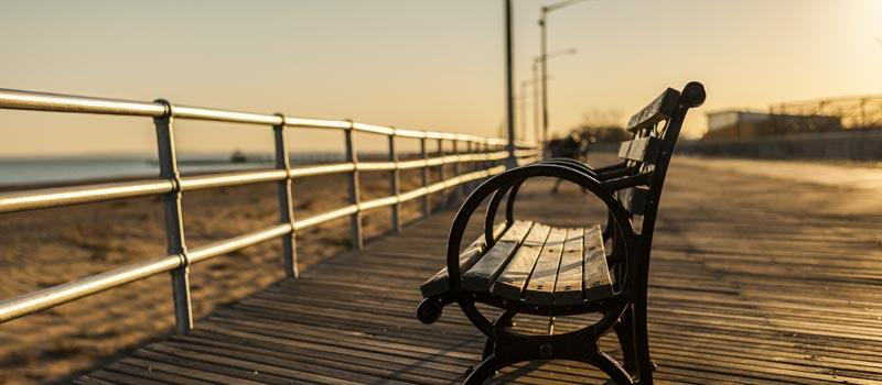 Shot of a bench facing the beach at Brighton Beach boardwalk in the evening