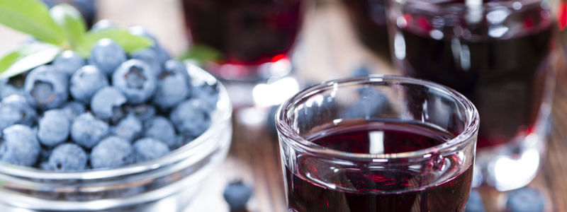 Blueberry Liqueur with some fresh fruits in a small glass